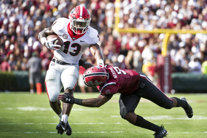 Georgia running back Elijah Holyfield (13) runs with the ball against South Carolina defensive back Keisean Nixon (9) during the first half of an NCAA college football game Saturday, Sept. 8, 2018, in Columbia, S.C. (AP Photo/Sean Rayford)