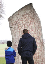 A father and a son look at a Viking-era runic stone near the Lake Vattern and the town of Odeshog, Sweden, Thursday Jan. 9, 2020. The stone dated to the 9th century could have been raised out of fear of a climate disaster, says a new study. (Jeppe Gustafsson/TT via AP)