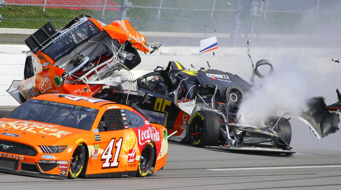 Chris Buescher, top left, gets airborne after a collision with Matt DiBenedetto (95) on the back stretch during a NASCAR Cup Series auto race at Talladega Superspeedway, Sunday, April 28, 2019, in Talladega, Ala. (AP Photo/Greg McWilliams)