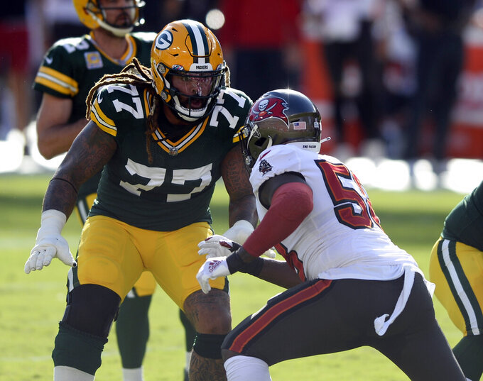 FILE - In this Oct. 18, 2020, file photo, Green Bay Packers offensive tackle Billy Turner (77) looks to block Tampa Bay Buccaneers outside linebacker Shaquil Barrett (58) during the first half of an NFL football game in Tampa, Fla. Turner has started six games at right tackle and three at left tackle this season. (AP Photo/Jason Behnken, File)