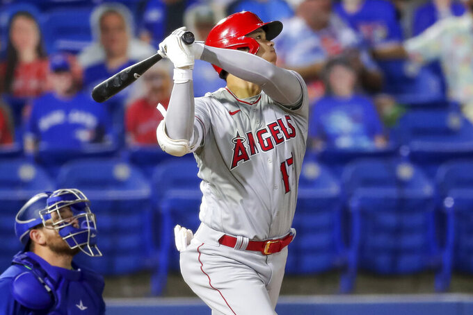 Los Angeles Angels' Shohei Ohtani watches his solo home run in front of Toronto Blue Jays catcher Alejandro Kirk during the fifth inning of a baseball game Friday, April 9, 2021, in Dunedin, Fla. (AP Photo/Mike Carlson)