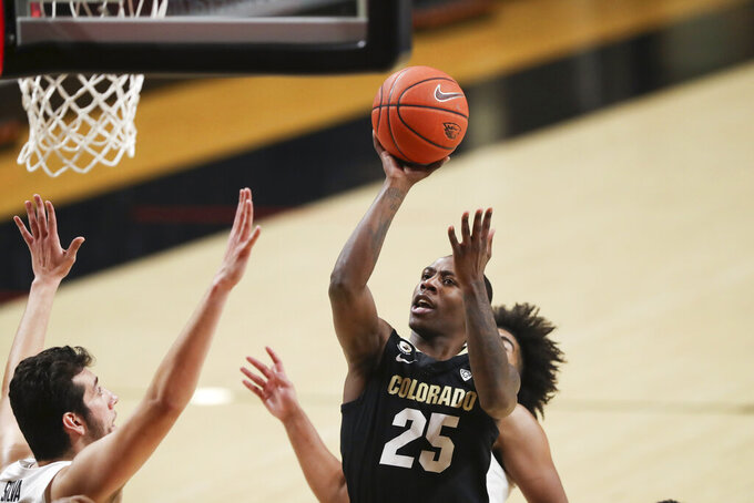 Colorado's McKinley Wright IV (25) shoots over Oregon State's Roman Silva, left, during the second half of an NCAA college basketball game in Corvallis, Ore., Saturday, Feb. 20, 2021. (AP Photo/Amanda Loman)