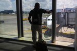 A passenger waits to board a humanitarian flight to Canada at the La Aurora international airport in Guatemala City, Thursday, Sept. 17, 2020. Authorities are preparing for the reopening of the airport on Friday as part of the gradual reopening of the country's borders by allowing national flights and some duly authorized international flights. (AP Photo/Moises Castillo)