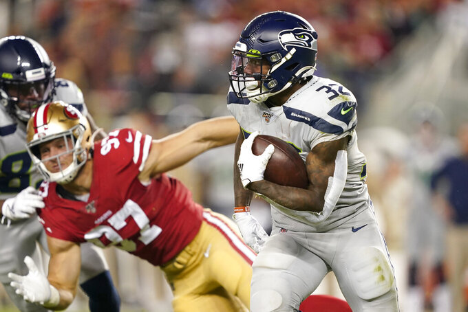 Seattle Seahawks running back Chris Carson (32) runs against San Francisco 49ers defensive end Nick Bosa (97) during the first half of an NFL football game in Santa Clara, Calif., Monday, Nov. 11, 2019. (AP Photo/Tony Avelar)