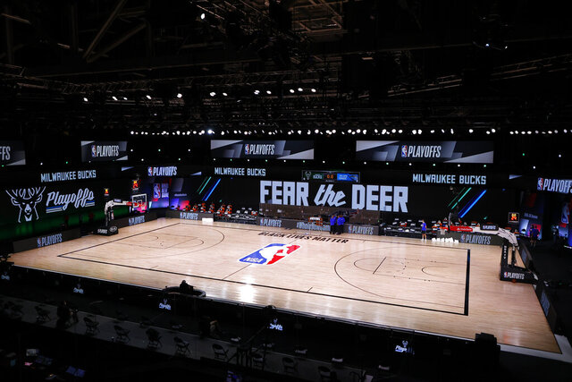 Referees huddle on an empty court at game time of a scheduled game between the Milwaukee Bucks and the Orlando Magic for Game 5 of an NBA basketball first-round playoff series, Wednesday, Aug. 26, 2020, in Lake Buena Vista, Fla. (Kevin C. Cox/Pool Photo via AP)