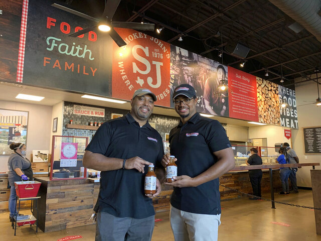 Juan Reeves, VP of Smokey John's BBQ, left, and his brother Brent Reeves, President of Smokey's John's BBQ, hold bottles of their famous barbecue sauce, which is available by mail order, at Smokey John's BBQ in Dallas on Dec. 10, 2020. (Jordyn Courtney/Smokey John's via AP)