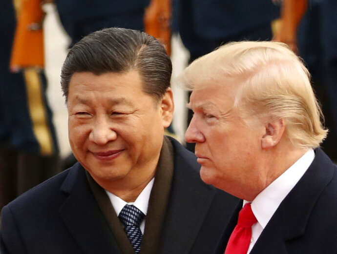 FILE - In this Nov. 9, 2017, file photo, U.S. President Donald Trump and Chinese President Xi Jinping participate in a welcome ceremony at the Great Hall of the People in Beijing, China. Xi had an