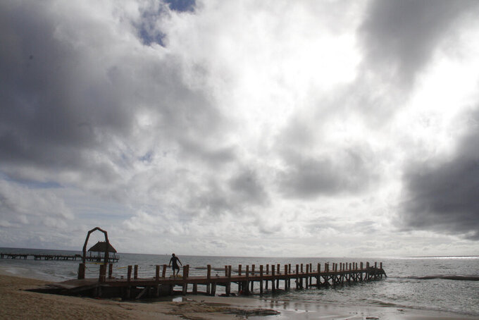 A worker secures a dock before Hurricane Delta arrives near Playa del Carmen, Mexico, early Tuesday, Oct. 6, 2020. Hurricane Delta rapidly intensified into a Category 2 hurricane Tuesday on a course to hammer southeastern Mexico and then grow to a potentially catastrophic Category 4 on approach to the U.S. Gulf Coast this week. (AP Photo/Tomas Stargardter)