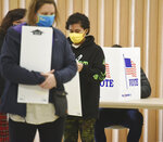 FILE - In this Nov. 3, 2020 file photo, residents wear masks as they vote at the Zion St. Joe United Church of Christ on Election Day, in St. Joseph, Mich. The leaders of three-dozen major Michigan-based companies, including General Motors and Ford, announced Tuesday, April 13, 2021, their opposition to Republican-sponsored election bills that would make it harder to vote in Michigan and other states. (Don Campbell/The Herald-Palladium via AP, File)