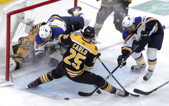 St. Louis Blues' Sammy Blais (9) crashes into Boston Bruins goaltender Tuukka Rask (40), of Finland, as Bruins' Brandon Carlo (25) and Blues' David Perron (57) grapple for the puck during the first period in Game 2 of the NHL hockey Stanley Cup Final, Wednesday, May 29, 2019, in Boston. (AP Photo/Charles Krupa)