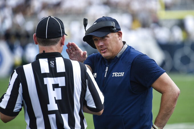 Georgia Tech coach Geoff Collins confers with an official during the second half of the team's NCAA college football game against South Florida on Saturday, Sept. 7, 2019, in Atlanta. Georgia Tech won 14-10. (AP Photo/Jon Barash)