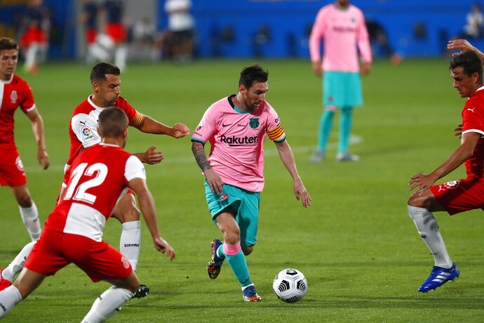 Barcelona's Lionel Messi, centre, in action during the pre-season friendly soccer match between Barcelona and Girona at the Johan Cruyff Stadium in Barcelona, Spain, Wednesday, Sept. 16, 2020. (AP Photo/Joan Monfort)