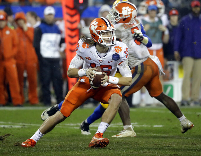 File-This Dec. 1, 2018, file photo shows Clemson's Trevor Lawrence (16) scrambling against Pittsburgh in the second half of the Atlantic Coast Conference championship NCAA college football game in Charlotte, N.C.  (AP Photo/Chuck Burton, File)