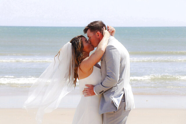 In this Friday, April 10, 2020, photo provided by Amy Fowler Shores, Savannah Kulenic and Dylan Perkins kiss during their wedding ceremony on a North Carolina beach. A jewelry company said it could overnight the groom's ring, but it was going to arrive after the ceremony. FedEx driver Joe Engel saw a note on the bride's door and took the package to the beach just in time. The couple was supposed to get married in Hawaii but canceled their destination ceremony amid the coronavirus pandemic. (Amy Fowler Shores via AP)