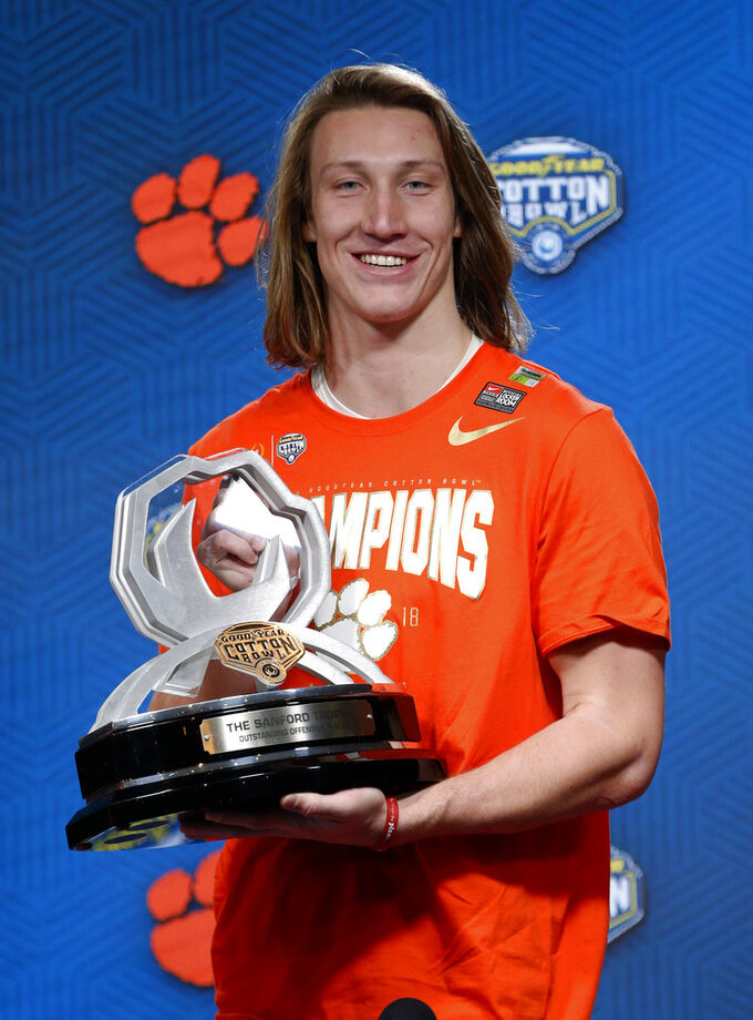 Clemson's Trevor Lawrence poses for photos with The Sanford Trophy Outstanding Offensive Player award at a news conference after their NCAA Cotton Bowl semi-final playoff football game against Notre Dame on Saturday, Dec. 29, 2018, in Arlington, Texas. Clemson won 30-3. (AP Photo/Michael Ainsworth)