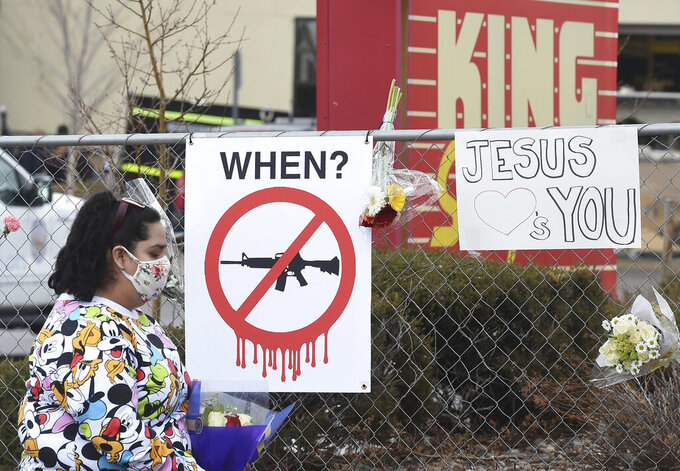 Tanice Cisneros walks by an anti-gun sign on the way to leave flowers for her friend, Rikki Olds on Tuesday, March 23, 2021. Olds was a King Soopers employee that was killed at the Boulder King Soopers on Monday.  (Jerilee Bennett/The Gazette via AP)