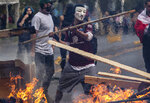 A demonstrator wearing a mask throws a plank of wood into a flaming barricade during anti-government protests in Santiago, Chile, Saturday, Oct. 19, 2019. The protesters have demanded improvements in education, health care and wages. Education, medicine and water in Chile are costly, and many families live on just $550 to $700 a month in earnings. (AP Photo/Esteban Felix)