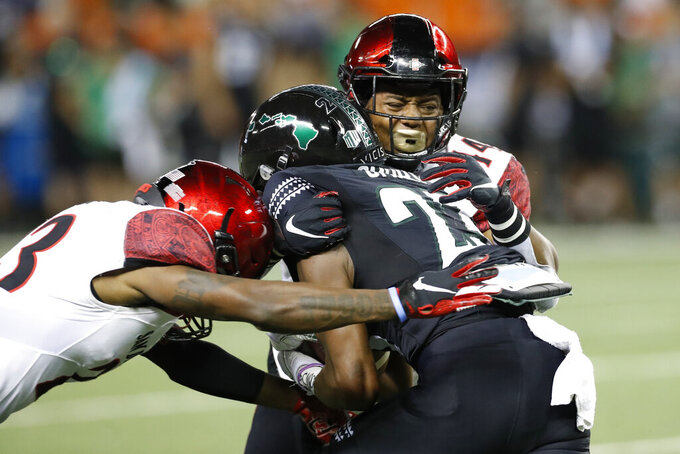 San Diego State cornerback Darren Hall (23) and linebacker Kyahva Tezino (44) tackle Hawaii wide receiver Jared Smart (23) during the first half of an NCAA college football game Saturday, Nov. 23, 2019, in Honolulu. (AP Photo/Marco Garcia)