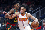Phoenix Suns guard Devin Booker (1) drives against Atlanta Hawks forward Cam Reddish (22) in the first half of an NBA basketball game Tuesday, Jan. 14, 2020, in Atlanta. (AP Photo/John Bazemore)