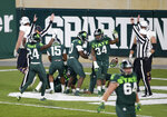 Michigan State players celebrate after scoring a touchdown on a fumbled Northwestern lateral as time expires during the fourth quarter of an NCAA college football game, Saturday, Nov. 28, 2020, in East Lansing, Mich. (AP Photo/Al Goldis)