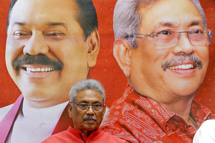 In this Nov. 6, 2019 photo, Sri Lankan presidential candidate and former defense chief Gotabaya Rajapaksa is seated next to a billboard carrying portraits of him self and his brother Mahinda at his residence in Colombo, Sri Lanka. Sri Lankans will be voting Saturday for a new president after weeks of campaigning that largely focused on national security and religious extremism in the backdrop of the deadly Islamic State-inspired suicide bomb attacks on Easter Sunday. (AP Photo/Eranga Jayawardena)