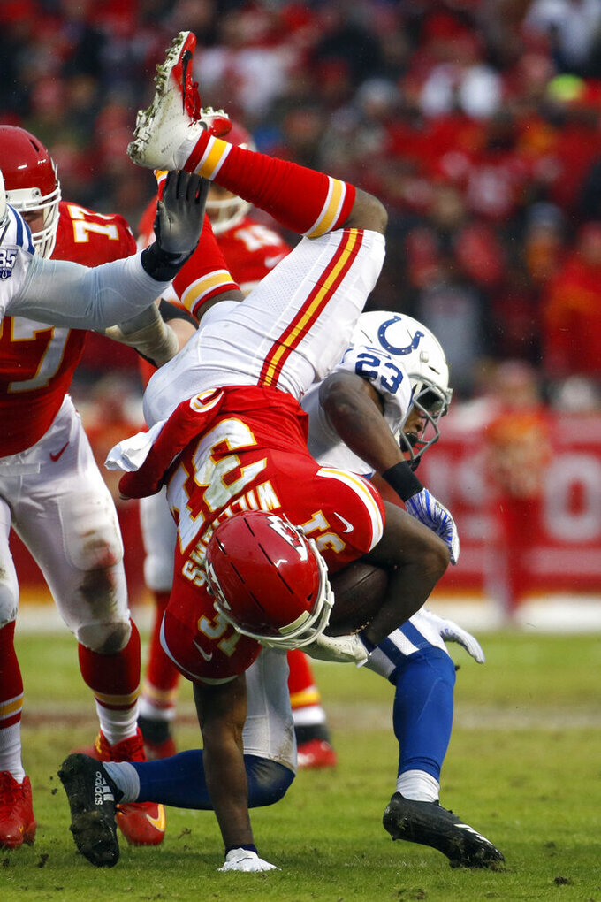 Kansas City Chiefs running back Darrel Williams (31) is flipped on a tackle by Indianapolis Colts cornerback Kenny Moore (23) during the first half of an NFL divisional football playoff game in Kansas City, Mo., Saturday, Jan. 12, 2019. (AP Photo/Charlie Riedel)