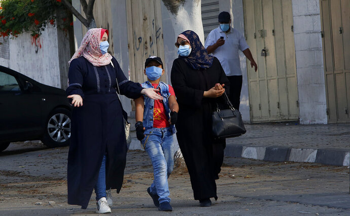 Palestinians wear face masks during a lockdown imposed following the discovery of a rise in coronavirus cases in Gaza City, Monday, Aug. 31, 2020.  (AP Photo/Hatem Moussa)