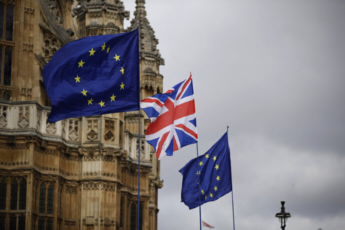 European flags and a British Union flag placed by anti-Brexit remain in the European Union supporters are blown by the wind across the street from the Houses of Parliament, not pictured, backdropped by Westminster Abbey in London, Monday, March 18, 2019. British Prime Minister Theresa May was making a last-minute push Monday to win support for her European Union divorce deal, warning opponents that failure to approve it would mean a long — and possibly indefinite — delay to Brexit. Parliament has rejected the agreement twice, but May aims to try a third time this week if she can persuade enough lawmakers to change their minds. (AP Photo/Matt Dunham)