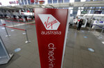 A sign is displayed at empty check-in counters for Virgin Australia at Sydney Airport in Sydney, Wednesday, Aug. 5, 2020. Virgin Australia will cut about 3000 jobs as the airline struggles with the effects of the coronavirus pandemic. (AP Photo/Rick Rycroft)