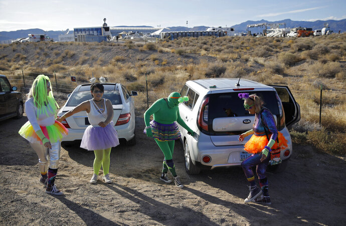 From left, Alex Clark, Carolyn Milner, Audrie Clark and Lucinda Clark dance near their car outside of the Storm Area 51 Basecamp event Friday, Sept. 20, 2019, in Hiko, Nev. The event was inspired by the