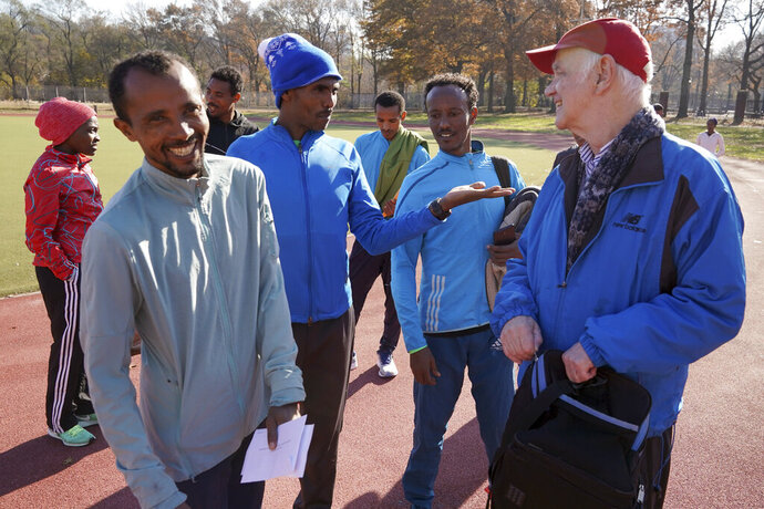 Bill Staab, right, talks with a group of Ethiopian runners after a short workout at Van Cortlandt Park in the Bronx borough of New York, Tuesday, Nov. 26, 2019. Girma Bekele Gebre stunned the elite field at the New York City Marathon by finishing third as a nonelite entrant in November. It was a life-changing performance for the Ethiopian runner, and one made possible because of his involvement with the West Side Runners' Club. Staab, the team president, has spent four decades helping immigrant runners acquire visas and gain entry to U.S. races, spending nearly $1 million of his own money to cover fees. Bekele Gebre is his greatest success, but not nearly the only runner he's helped. (AP Photo/Seth Wenig)