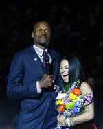 Naismith Memorial Basketball Hall of Famer Ray Allen, left, and his wife Shannon Walker Williams stand together as Allen's number is retired to the rafters during a halftime ceremony at an NCAA college basketball game between South Florida and Connecticut, Sunday, March 3, 2019, in Storrs, Conn. (AP Photo/Steven Senne)