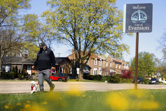 """A person walks a dog past a street sign reading """"Welcome to Evanston"""" in the predominantly Black 5th Ward in Evanston, Ill., Tuesday, May 4, 2021. The Chicago suburb is preparing to pay reparations in the form of housing grants to Black residents who experienced housing discrimination. (AP Photo/Shafkat Anowar)"""