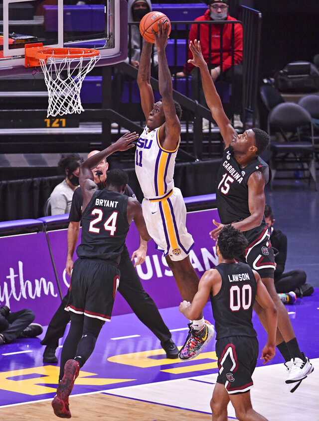 LSU forward Josh LeBlanc Sr. (11) dunks the ball over South Carolina forward Keyshawn Bryant (24) and South Carolina center Wildens Leveque (15), during an NCAA college basketball game, Saturday, Jan. 16, 2021, in Baton Rouge, La.  (Hilary Scheinuk/The Advocate via AP)