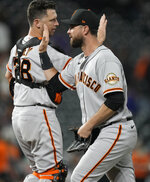 San Francisco Giants first baseman Brandon Belt, front, is congratulated by catcher Buster Posey after the ninth inning of a baseball game against the Colorado Rockies Saturday, Sept. 25, 2021, in Denver. The Giants won 7-2. (AP Photo/David Zalubowski)