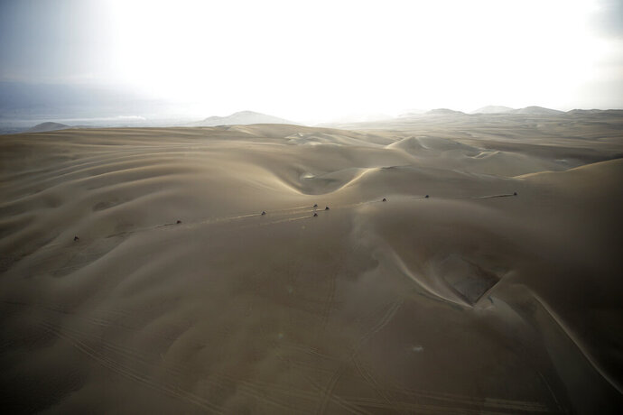 FILE - In this Jan. 16, 2019 photo, competitors ride their motorbikes across the dunes during stage nine of the Dakar Rally in Pisco, Peru. Dakar organizers say next year's cross-country race will be held in