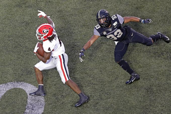 Georgia running back James Cook (4) gets past Vanderbilt safety Dashaun Jerkins (33) to score a touchdown on an 18-yard run in the first half of an NCAA college football game Saturday, Aug. 31, 2019, in Nashville, Tenn. (AP Photo/Mark Humphrey)