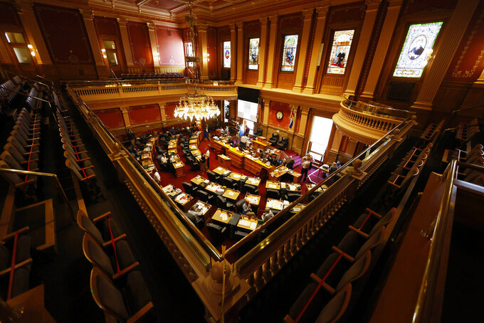 FILE - In this June 15, 2020, file photo, is an overhead view of the Senate chambers in the State Capitol in Denver. A Colorado state Senate panel is hearing testimony on a bill to grant minimum wage and overtime rights to thousands of farmworkers and allow those workers to organize and join labor unions. The bill, sponsored by three Democrat lawmakers, would regulate working hours for overtime, rest and eating breaks, and guarantee farmworkers living space that conforms with health guidelines to stem the spread of the coronavirus. (AP Photo/David Zalubowski, file)