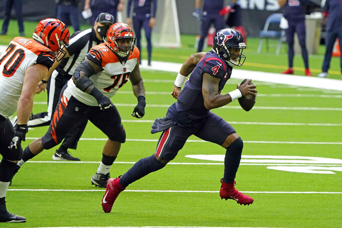 Houston Texans quarterback Deshaun Watson (4) rushes for a gain as Cincinnati Bengals' Margus Hunt (70) and Mike Daniels (76) defend during the second half of an NFL football game Sunday, Dec. 27, 2020, in Houston. (AP Photo/Eric Christian Smith)