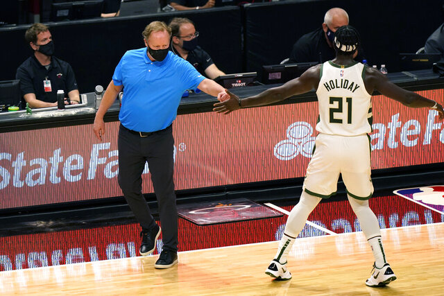 Milwaukee Bucks coach Mike Budenholzer, left, uses his fist to bump the hand of Jrue Holiday (21) during the first half of the team's NBA basketball game against the Miami Heat, Tuesday, Dec. 29, 2020, in Miami. (AP Photo/Lynne Sladky)