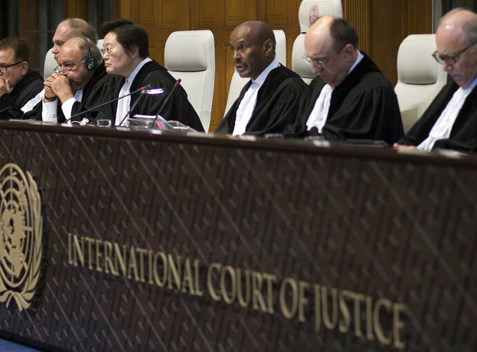FILE - In this Wednesday, Feb. 13, 2019 file photo, Presiding judge Abdulqawi Ahmed Yusuf of Somalia, third right, reads the court's verdict at the International Court of Justice, or World Court, in The Hague, Netherlands. The United Nations' highest court on Friday, Nov. 8 says it has jurisdiction in a case brought by Ukraine that alleges Russia breached treaties on terrorist financing and racial discrimination by arming rebels in eastern Ukraine and reining in the rights of ethnic Tartars and other minorities following its annexation of the Crimea. The court's president, Abdulqawi Yusuf, says the ruling was limited to jurisdiction and does not address the merits of Ukraine's complaints in the case.(AP Photo/Peter Dejong, file)