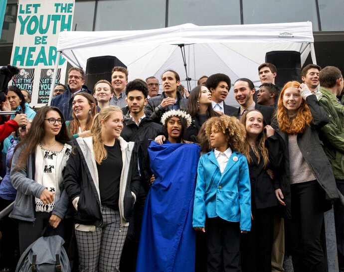 FILE - In this Oct. 29, 2018, file photo, young plaintiffs stand on the steps of the United States District Courthouse during a rally in Eugene, Ore., to support a high-profile climate change lawsuit against the federal government. A lawsuit by a group of young Americans accusing the U.S. government of harming them by having fostered a fossil-fuels energy system faces a major hurdle Tuesday, June 4, 2019, when a federal appeals court hears oral arguments on whether the case should proceed. (Andy Nelson/The Register-Guard via AP, File)
