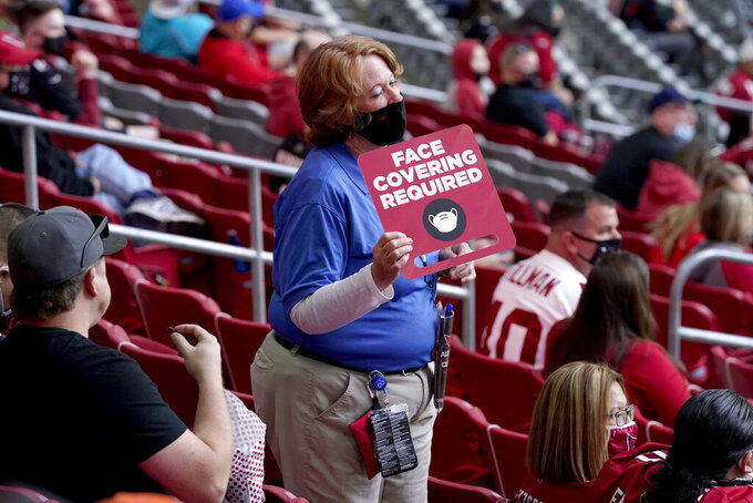 An Arizona Cardinals guest relations attendant highlights face mask requirements to fans during the second half of an NFL football game against the Miami Dolphins, Sunday, Nov. 8, 2020, in Glendale, Ariz. (AP Photo/Ross D. Franklin)