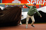 Members of the Atlanta Braves grounds crew work to cover the infield before a baseball game between Atlanta Braves and Colorado Rockies was cancelled because of rain Thursday, Sept. 16, 2021, in Atlanta. (AP Photo/John Bazemore)
