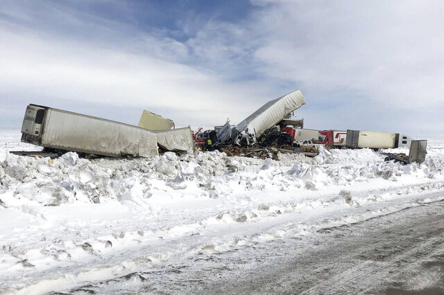 Wrecked tractor-trailers remain on the scene Monday, March 2, 2020, following Sunday's accident, on Interstate 80 in south central Wyoming. Multiple people died and dozens were injured in the pileup that happened amid blowing snow on a highway that stretches across the state. (Wyoming Highway Patrol via AP)