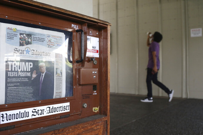 FILE - A man walks past a newspaper stand at the international airport in Honolulu on Friday, Oct. 2, 2020. The coronavirus pandemic, a high-stakes U.S. election and a racial reckoning expanded news audiences for many newspapers and TV news channels, making 2020 a blockbuster news year. But it was terrible for the newspaper industry's finances and the public that relies on original reporting to inform them on their local government and community, and that's not likely to change in 2021. (AP Photo/Caleb Jones, file)