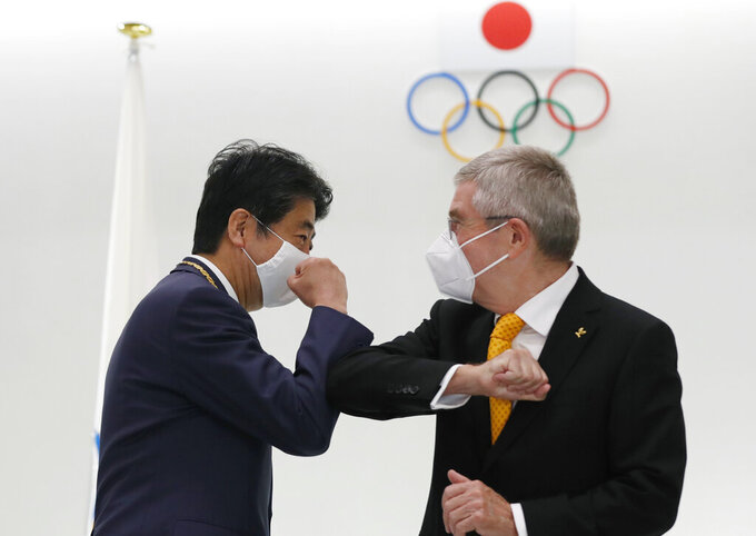 Former Japan's Prime Minister Shinzo Abe, left, and Thomas Bach, President of the International Olympic Committee (IOC), bump elbows after a ceremony to present the Olympic Order to Abe at Japan Olympic Museum in Tokyo Monday, Nov. 16, 2020. (Kim Kyung-hoon/Pool Photo via AP)