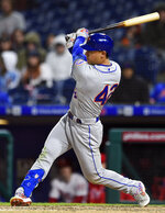 New York Mets' Michael Conforto watches the ball after hitting an infield hit off Philadelphia Phillies' Pat Neshek that scored Juan Lagares during the 11th inning of a baseball game against the Philadelphia Phillies, Monday, April 15, 2019, in Philadelphia. The Mets won 7-6. (AP Photo/Derik Hamilton)