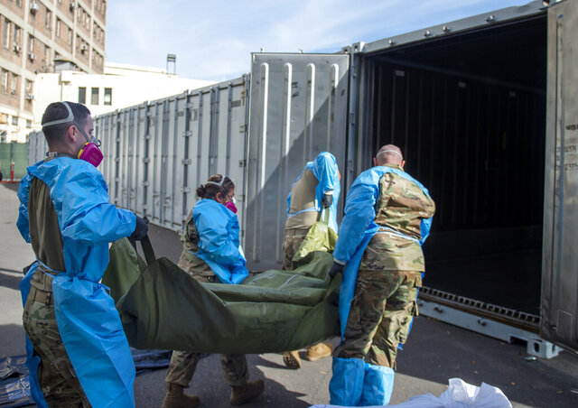 FILE - This Jan. 12, 2021, file photo provided by the LA County Dept. of Medical Examiner-Coroner shows National Guard members assisting with processing COVID-19 deaths and placing them into temporary storage at LA County Medical Examiner-Coroner Office in Los Angeles in Los Angeles. More than 500 people are dying each day in California because of the coronavirus. The death toll has prompted state officials to send more refrigerated trailers to local governments to act as makeshift morgues. State officials said Friday they have helped distribute 98 refrigerated trailers to help county coroners store dead bodies. California reported 669 COVID-19 deaths, the second-highest daily death count, on Saturday, Jan. 16, and the nation's most populous county announced it had detected its first case of a more transmissible strain of the coronavirus. Public health authorities in Los Angeles County confirmed its first case of the variant of COVID-19 first detected in the United Kingdom. It was iden