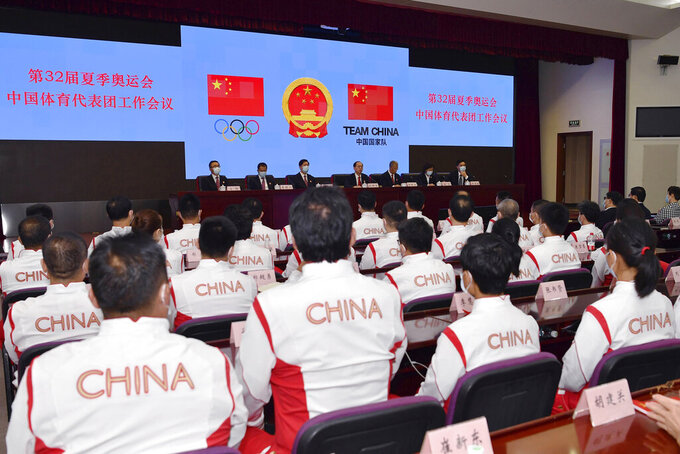 In this photo released by Xinhua News Agency, Chinese delegation for the upcoming Tokyo 2020 Olympic Games attend a meeting in Beijing, China on Wednesday, July 14, 2021. China will send 431 athletes to the Tokyo Games as part of a 777-member delegation, its largest at an Olympics outside China, the official Xinhua News Agency said Wednesday. (Tao Xiyi/Xinhua via AP)